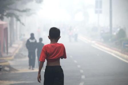 Seorang anak berjalan menembus pekatnya kabut asap di Jalan Sultan Sahrir Pangkalan Bun. BI Sebut produksi kelapa sawit selama kabut asap turun.
