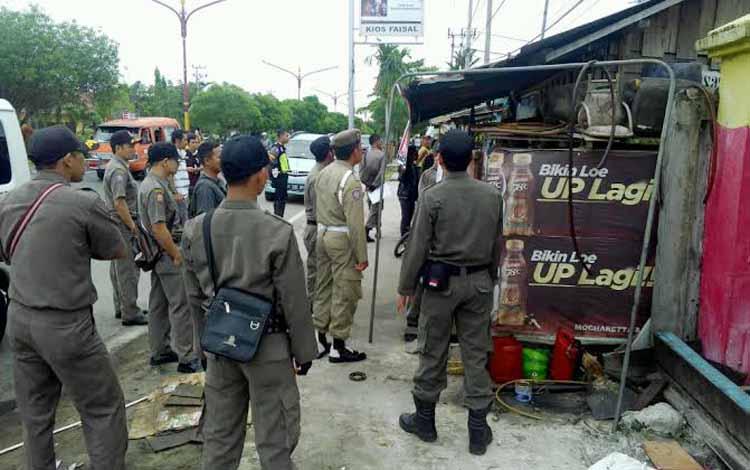PENERTIBAN PEDAGANG: Apaarat Satpol PP Kota Palangka Raya menertibkan kios di Jalan RT A Milono, Kamis (9/5/2016). Para pedagang tidak boleh melanggar jalur hijau. Mereka tak diperkenankan berjualan di atas drainase. BORNEO/BUDI YULIANTO.