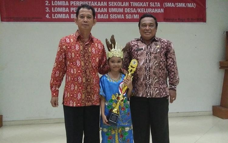 Kepala KPAD Barsel, Ardi (kiri), Kepala Perpustakaan Kalteng (kanan) mengapit Isma Putri, juara pertama Lomba Bercerita tingkat Provinsi Kalimantan Tengah, di Palangka Raya, Kamis (19/5/2016). BORNEO/URIUTU DJAPER