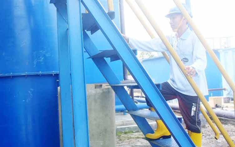 Petugas PDAM sedang menaiki tangki pengolahan air bersih. BORNEONEWS/WAHYU KRIDA