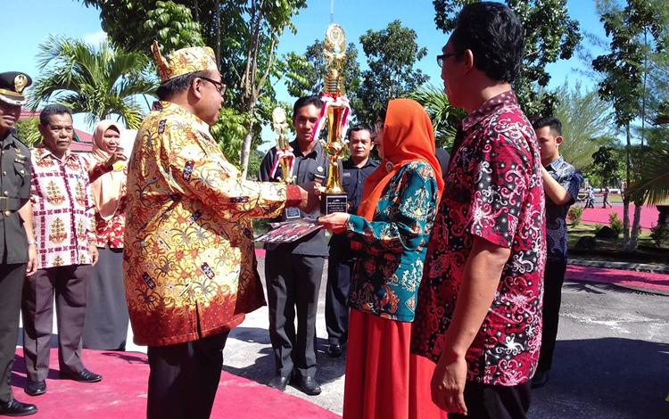 Bupati Sukamara, Ahmad Dirman menyerahkan piala penghargaan kepada Kepala Sekolah Madrasah Aliyah (MA) Sukamara yang berhasil meraih juara pertama lomba perputakaan sekolah tingkat provinsi. (foto: noorhasanah)