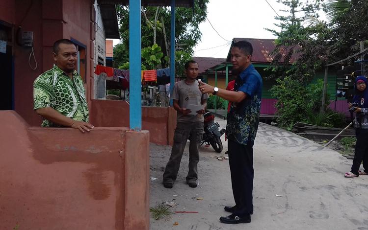 Kepala Badan Lingkungan Hidup (BLH) Sukamara, Iwan Miraza meninjau  permukiman warga yang terkena limbah oli. BORNEONEWS/NORHASANAH