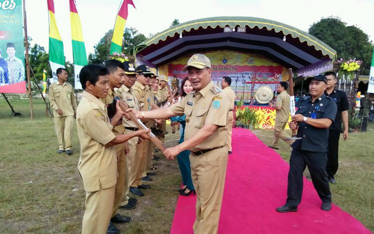 Bupati Lamandau Marukan (tengah bertopi), menyerahkan cangkul kepada perwakilan pemerintah desa Bhina Bakti, simbol dimulainya BBGRM tingkat Kabupaten Lamandau 2016. BORNEONEWS/HENDI NURFALAH