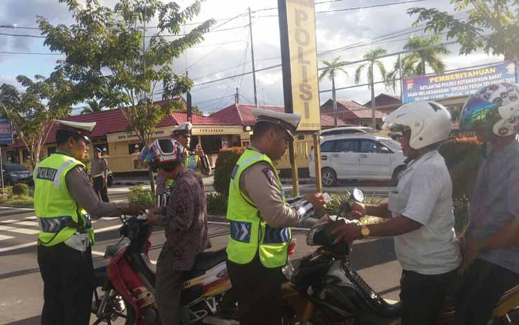 Anggota Satlantas Polres Kobar memeriksa surat-surat kendaraan milik pengendara di jalan Diponegoro, Pangkalan Bun. Rata-rata, polisi menilang 83 pengendara perhari.   BORNEONEWS/CECEP HERDI