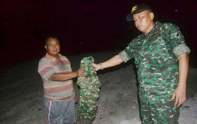 Seorang penambang menyerahkan pakaian loreng yang sebelumnya dipakai menambang kepada Perwira Penghubung Kodim 1015 Sampit di Kasongan Mayor Inf Mahsun Abadi. BORNEONEWS/ABDUL GOFUR