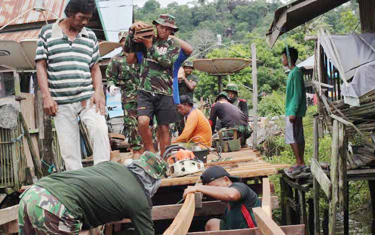 Anggota TNI bersama warga membangun jembatan titian berbahan kayu sepanjang 150 meter di Jalan Mangku Mambang, Kelurahan Tangkiling Kecamatan Bukit Batu Palangka Raya. (BORNEONEWS/FERRY FATALA)