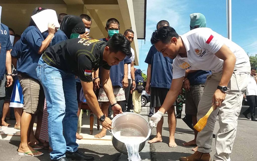 Dua anggota Satreskoba Polres Kotawaringin Timur sedang membuang air bekas pemusnahan barang bukti sabu yang mereka sita ke dalam selokan di hadapan para tersangka yang menjadi pemiliknya. BORNEONEWS/M HAMIM