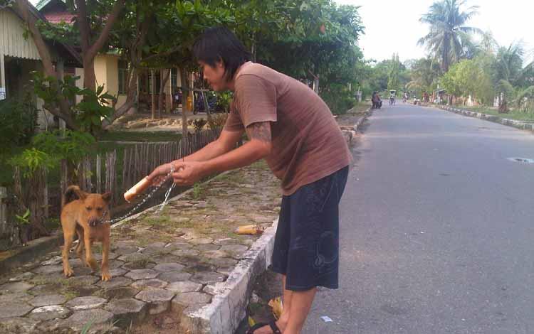 Seorang warga pemilik anjing sedang membawa anjingnya berjalan-jalan. BORNEONEWS/URIUTU DJAPER