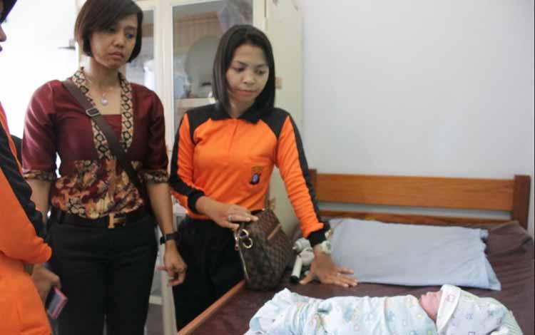 Anggota Polwan Polres Kotawaringin Timur melihat  kondisi bayi yang ditemukan warga di pagar rumahnya, saat berada di Puskesmas Baamang, Jumat (27/5/2016). BORNEONEWS/M. HAMIM