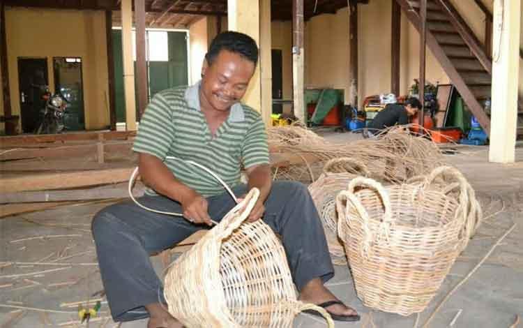 Seorang perajin rotan tengah membuat tempat sampah di pusat produksi dan kerajinan rotan Desa Hampangen Kecamatan Tasik Payawan, beberapa waktu lalu. BORNEONEWS/ABDUL GOFUR