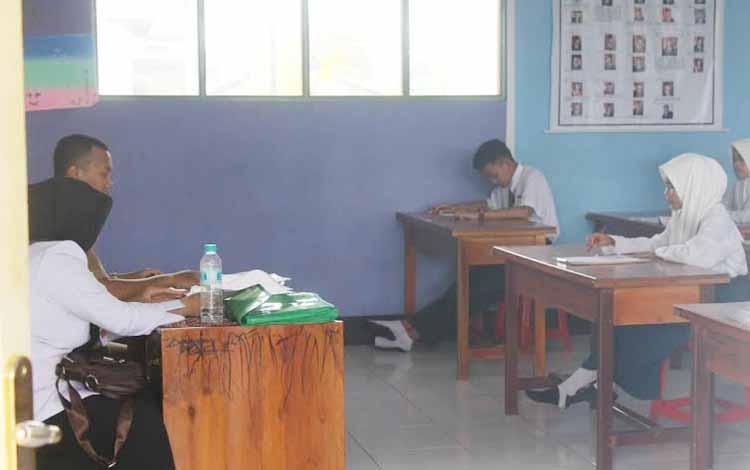 Dua orang guru mengawasi siswanya saat pelaksanaan ujian nasinal tingkat SMP yang berlangsung beberapa waktu lalu.