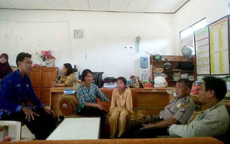 Pinati (tengah) bersama orang tuanya di ruang kantor SDN Mintin 2, didampingi Kepala Desa dan aparat kepolisian. Pinati lolos dari percobaan penculikan Senin (22/8/2016). BORNEONEWS/JAMES DONNY