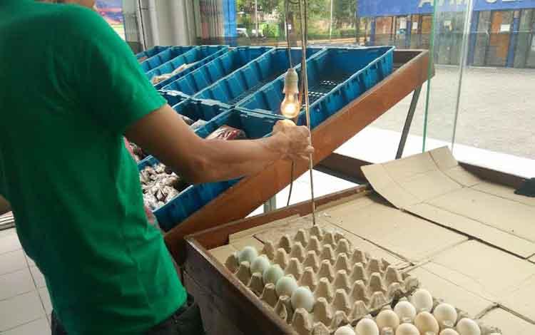 Tampak seorang calon pembeli memeriksa telur menggunakan lampu yang disediakan pihak pasar swalayan. DOK BORNEONEWS