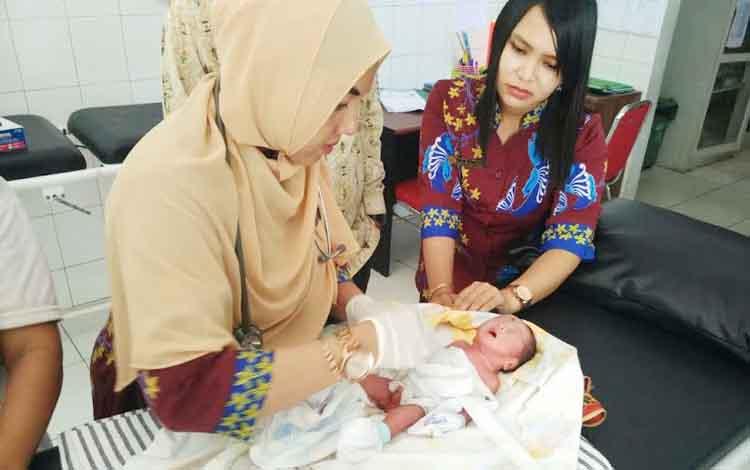Dua bidan dari Puskesmas Baamang sedang merawat bayi laki-laki yang ditemukan warga Jl Tjilik Riwut Km 8, Kecamatan Baamang, Kamis (23/2/2017).
