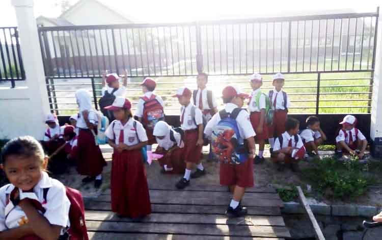 Sejumlah murid SDN 1 Baamang Barat duduk di depan pagar sekolahnya karena pagar tersebut terkunci. Sementara kuncinya dibawa kepala sekolah yang tak kunjung datang hingga pukul 07.00 WIB.