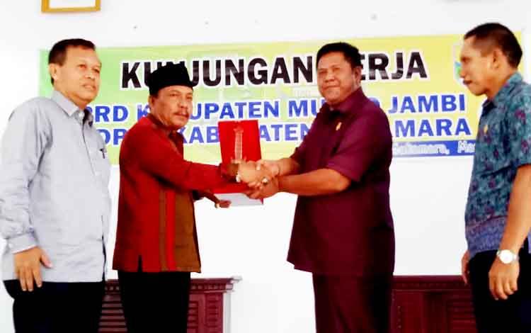 Wakil Ketua I DPRD Kabupaten Sukamara Daman Huri saat memberikan cendramata kepada Wakil Ketua DPRD Kabupaten Muora Jambi.