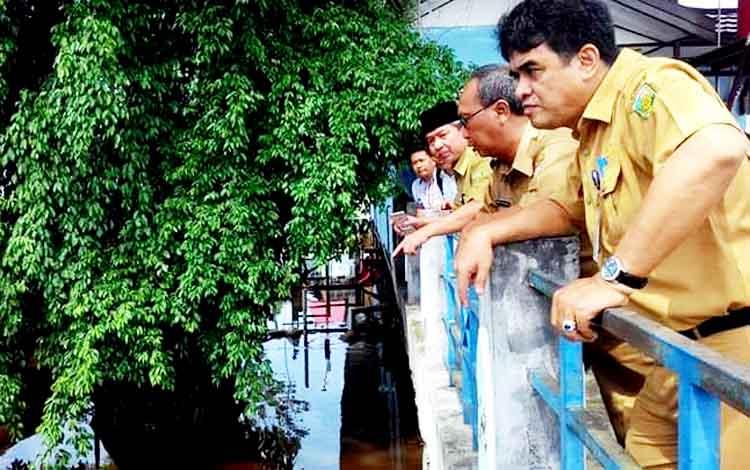 Rojikinnor Kepala Dinas Perumahan Rakyat dan Kawasan Pemukiman, Wakil Walikota Palangka Raya Mofit Saptono Subagio, dan Walikota Palangka Raya Riban Satia mengamati aliran Sungai Kahayan yang biasanya membawa sampah