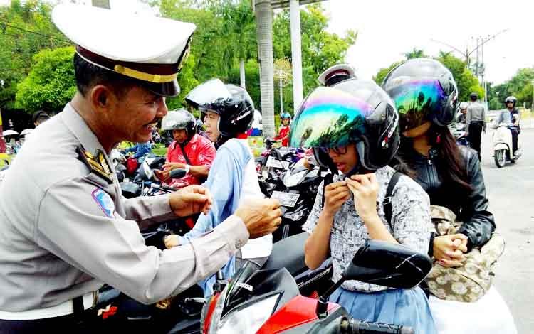 Anggota Ditlantas Polda Kalteng mengingatkan pelajar agar menggunakan helm dengan baik dan benar.