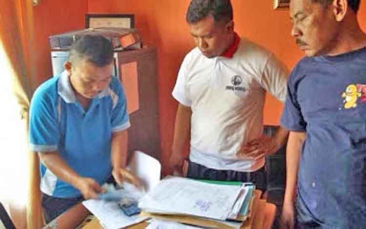 Karyadi (baju biru) saat menunjukan barang bukti uang kepada pihak kepolisian.