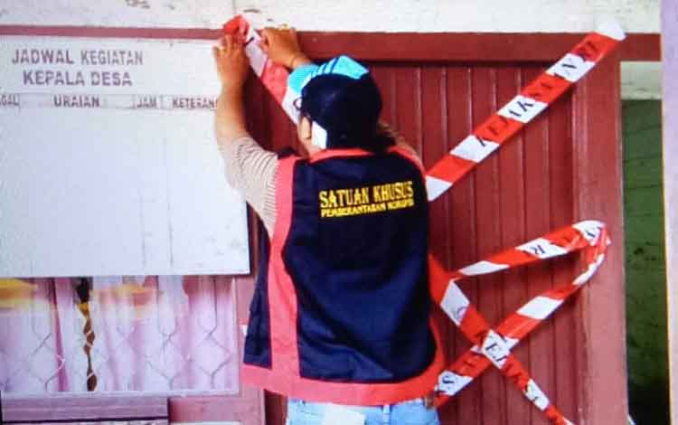 Petugas tim Saber Pungli Kejaksaan Negeri Seruyan aat memasang garis pengaman di depan ruang kerja Kepala Desa Pematang Limau.