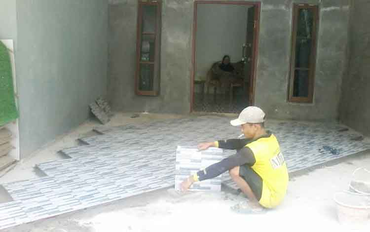 Seorang pekerja memasang keramik pada salah satu rumah warga Jalan Soekarno-Hatta Gang Saudara Kasongan, Kamis (27/4/2017).