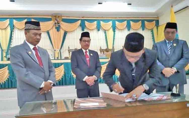 Ketua DPRD Lamandau, H. Tommy Hermal Ibrahim, disaksikan Bupati dan dua wakil ketu DPRD Lamandau saat menandatangani berkas naskah putusan DPRD tentang catatan strategis, Jumat (28/4/2017).