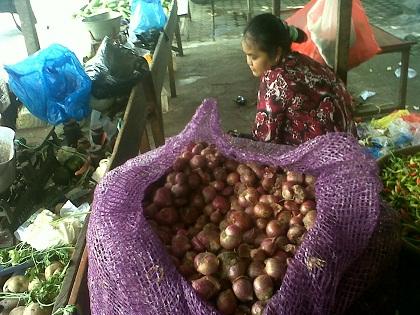 Seorang penjual sayur mayur yang juga menjual bawang merah di Pasar Kasongan\\r\\n