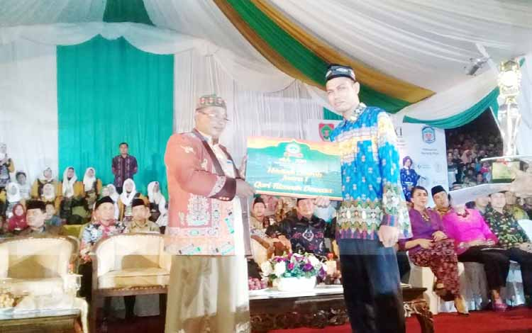 Wakil Gubernur Kalteng, Habib Haji Said Ismail menyerahkan secara simbolis hadiah kepada juara pertama lomba Tilawah dewasa asal Kafilah Barito Selatan, Muhamadun saat malam penutupan STQ di Kota Puruk Cahu, Kamis (18/5/2017).