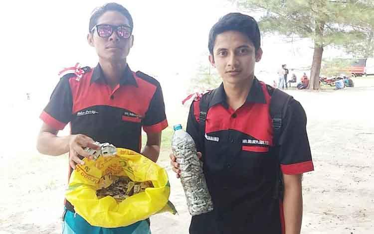 Dua orang anggota Mapala Universitas Darwan Ali (UNDA) saat menunjukkan bungkus Zenith di Pantai Ujung Pandaran, Minggu (17/7/2017)
