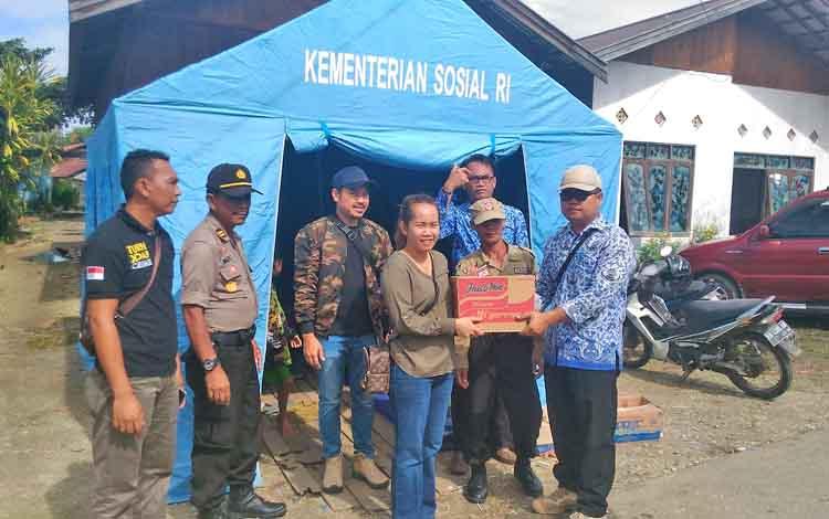 Anggota DPRD Gunung Mas Nomi Aprilia (kiri) secara simbolis menyerahkan bantuan kepada warga Lurah Tampang Tumbang Anjir Yeremia Dodi, Senin (17/7/2017)