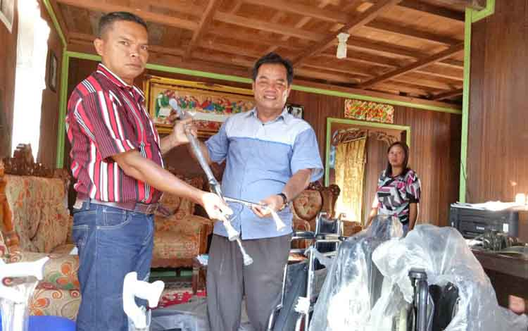 Anggota DPRD Gumas Untung Jaya Bangas (kanan) menyerahkan bantuan kepada masyarakat penyandang cacat, beberapa hari lalu.