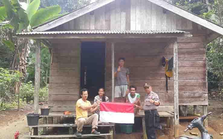 Kapolsek Balai Riam, Iptu Jampi Silaban membagikan bendera merah putih kepada warga Desa Lupu Peruca, Kecamatan Balai Riam, Sukamara.