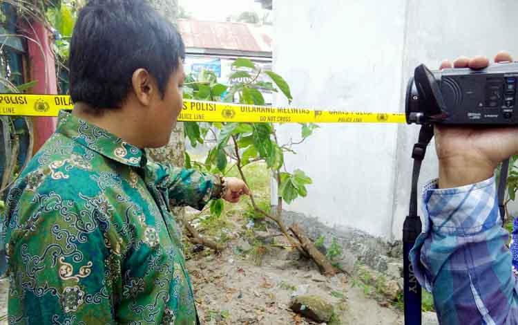 Heri Purwanto, guru SDN 2 Bukit Tunggal menunjukan pohon yang dipotong dan disiram minyak tanah. Lokasi sekitar sudah dipasang garis polisi