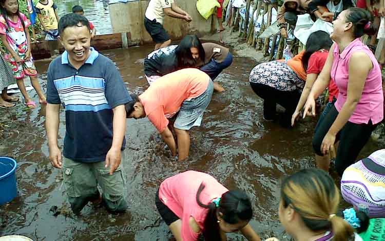 Para ibu-ibu dipimpin panitia (laki-laki) sedang berupaya menangkap ikan pada lomba tangkap ikan di Komplek Griya Ketimpun Indah, Kamis (17/8/2017).