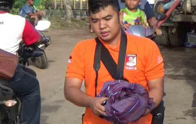 Seorang anggota Polres Kotim membawa barang bukti berupa kain merah yang ditemukan di samping pagar luar MAN Sampit, Minggu (20/8/2017)