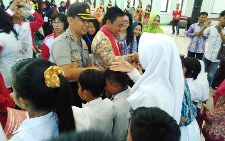 Bupati Edy Pratowo dan Kapolres Pulang Pisau AKBP Dedy Sumarsono menyalami anak-anak saat menghadiri peringatan Hari Anak Nasional.