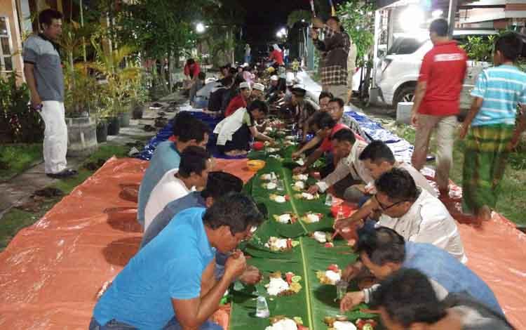Ratusan warga saat menyantap nasi liwet yang dibuat sepanjang 100 meter.