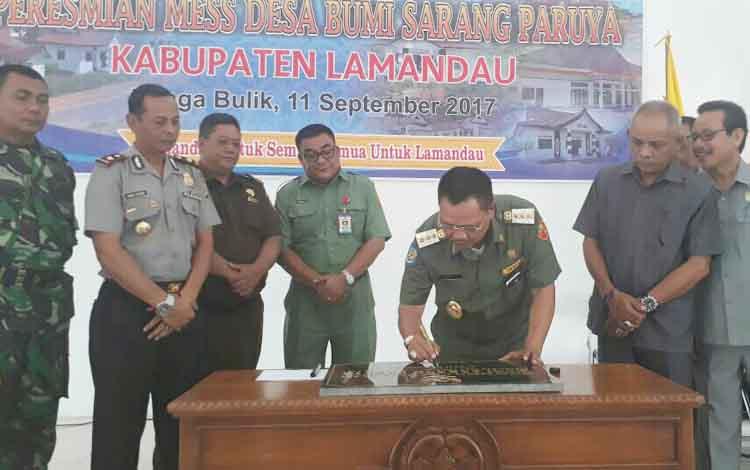Bupati Lamandau Marukan menandatangani prasasti simbol peresmian Mess Desa Sarang Paruya, di Aula Mess Desa, Senin (11/9/2017).