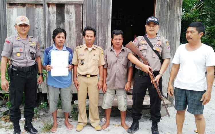 Kapolsek Manuhing Nanang Mauludi (paling kiri) saat menerima senjata api rakitan dari warga Desa Berang Jun