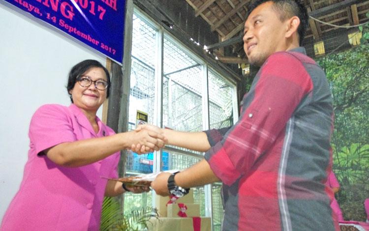 Ketua Bhayangkari Kalteng, Lina Anang Revandoko, menyerahkan bantuan dana adopsi yang diterima Manajer Program BOSF Nyaru Menteng, Denny Kurniawan, Kamis (14/9/2017).