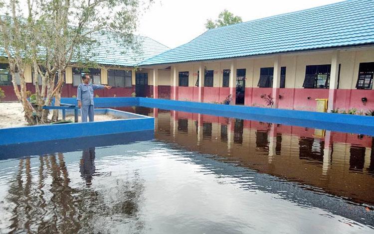 Kepala SMPN 3 Palangka Raya Gunarhad saat mengecek kolam ikan yang adan di halaman sekolah, Kamis (12/10/2017).