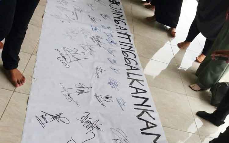 Puluhan alumni menggelar aksi solidaritas penggalangan tanda tangan sebagai bentuk dukungan moral terhadap guru mereka Abdul Kadir.