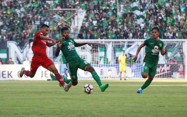 Rifaldi Bawuo (kaos merah) dibayang-bayangi empat pemain Persebaya Surabaya