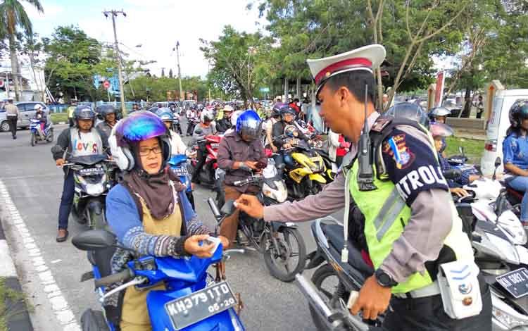 Polisi memberi tanda silang bagi pengendara yang dinyatakan lengkap, Senin (13/11/2017)