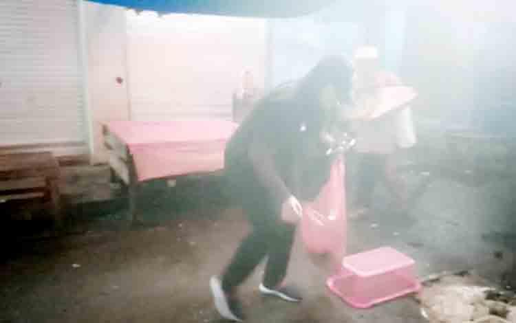 Ketua PPI Kapuas, Kusmiatie sedang memungut sampah yang ada di Pasar Blok R Kapuas.