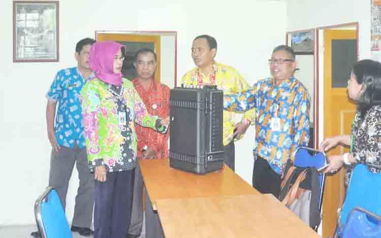 Sekretaris Diskominfo Kabupaten Kapuas Dr H Suwarno Muriyat M.Pd didampingi Kabid Persandian H Yahya memberi penjelasan tentang fungsi zimmer (alat sadap HP) kepada tamunya Rusmawarni Kabid Persandian Diskomsantik Provinsi Kalimantan Tengah yang bertandan