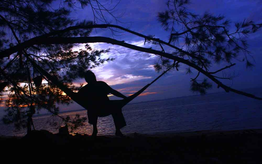 Pengunjung TWA Tanjung Keluang sedang bersantai sambil menggantungkan hammock