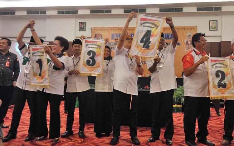 Paslon Pilkada Palangka Raya menunjukkan nomor urut.