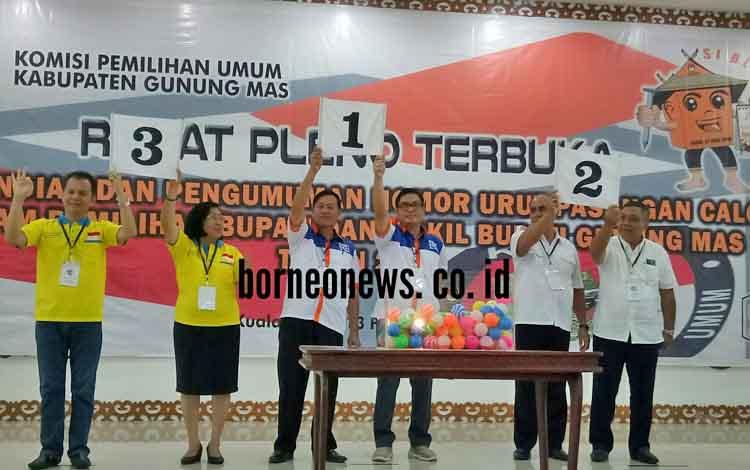 Tigas pasang calon bupati dan calon wakil bupati Gumas memperlihatkan nomor urut pasangan calon.