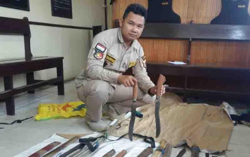 Petugas menunjukkan senjata tajam yang diamankan dari calon penumpang kapal.